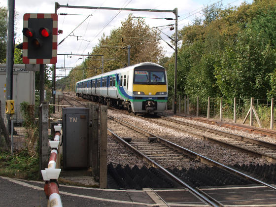An electric commuter train approaching a level crossing