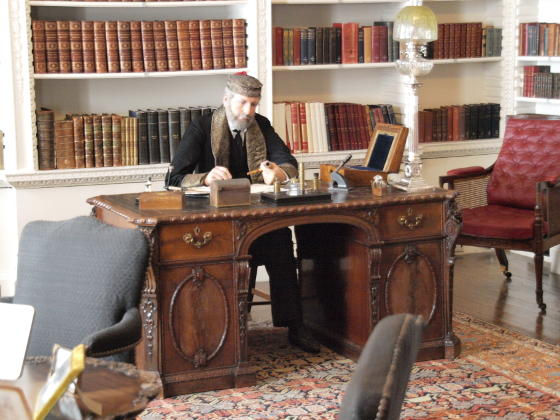 A waxwork of a man in a smoking cap and jacket sitting at a desk in a library