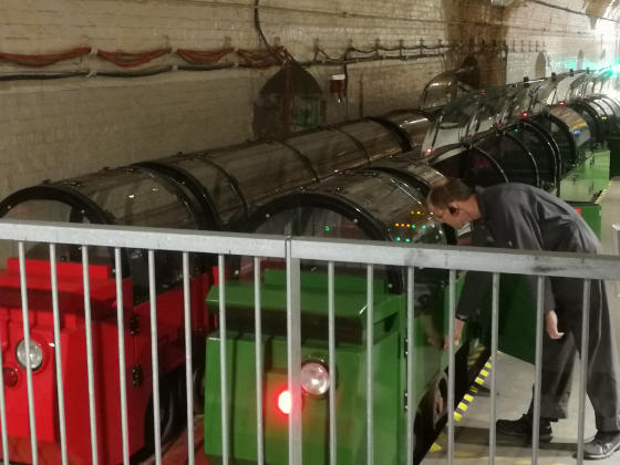 An engineer looking at some small railway carriages inside a tunnel