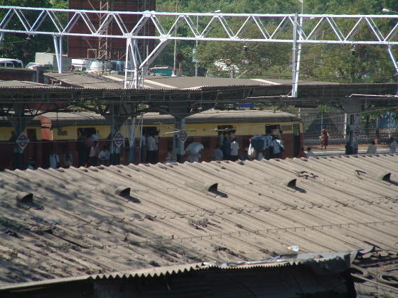 Looking over a corrugated roof to an Indian commuter train